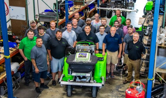 Steel Green Manufacturing Team Poses in Warehouse
