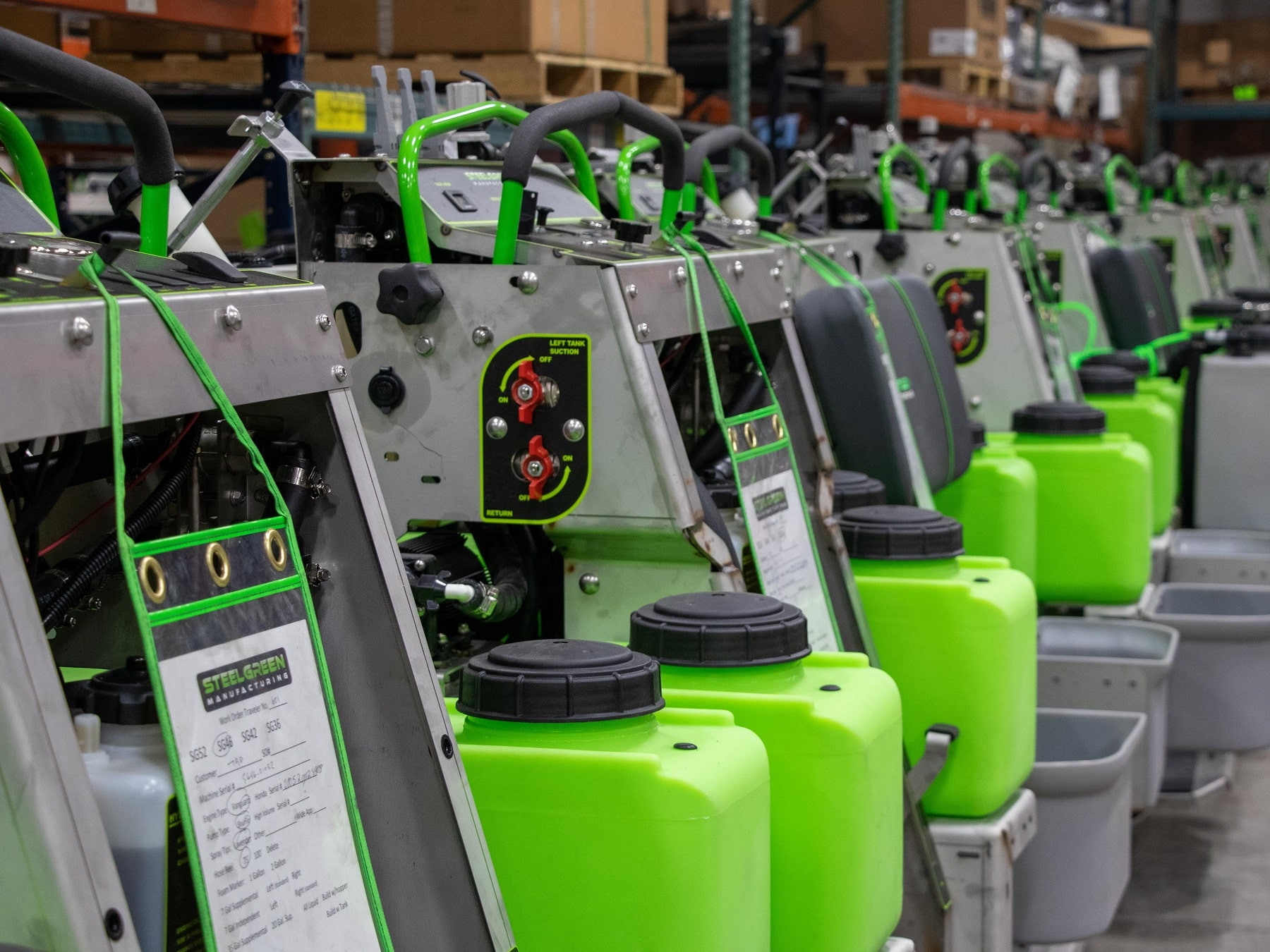 line up of steel green manufacturing sprayers